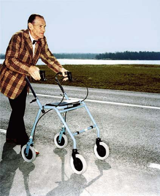 Photo of an old man with his walker on the road