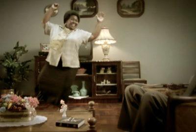 Woman dancing in living room in front of guest