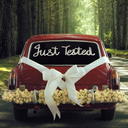 "Wedding car with message ""Just Tested"" on back window"